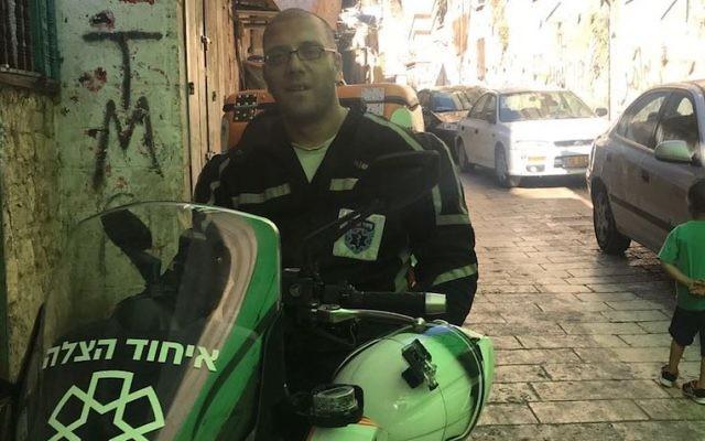 Nedal Sader assis sur son scooter d' United Hatzalah  dans la Vieille ville de Jérusalem, le 14 juillet 2017 (Crédit : Andrew Tobin)