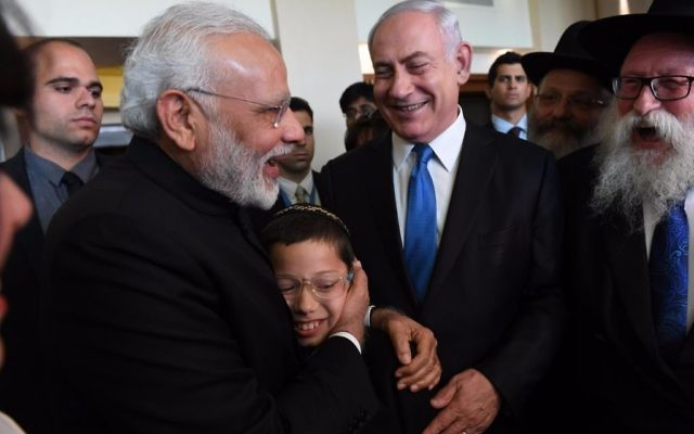Moshe Holtzberg, le fils de deux émissaires du Habad tués dans un attentat en novembre 2008 à Bombay dans les bras du Premier ministre indien Narendra Modi, avec le Premier ministre Benjamin Netanyahu, en Israël, le 5 juillet 2017. (Crédit : Raphael Ahren/Times of Israël)