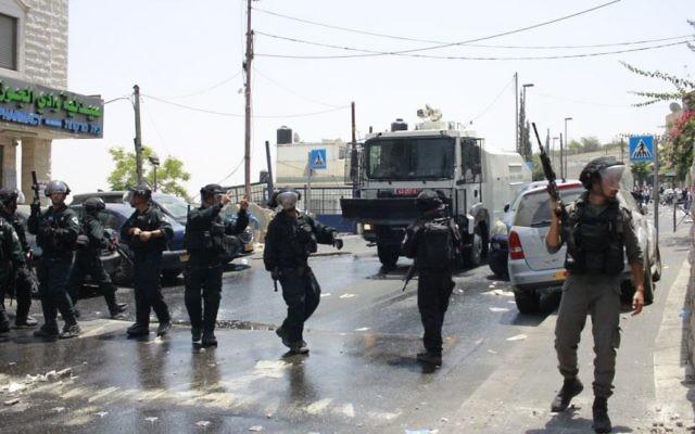 Les forces de sécurité israéliennes se tiennent devant les émeutiers palestiniens devant la porte des Lions le 21 juillet 2017 (Crédit : Judah Ari Gross / Times of Israel)