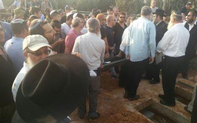 Des milliers de personnes se sont réunies dans le cimetière municipal de Modiin dans le centre d'Israël pour les funérailles des trois membres de la même famille assassinés ce week-end durant un attentat terroriste commis au sein de l'implantation de Halamish (Crédit : Raoul Wootliff/Times of Israel)