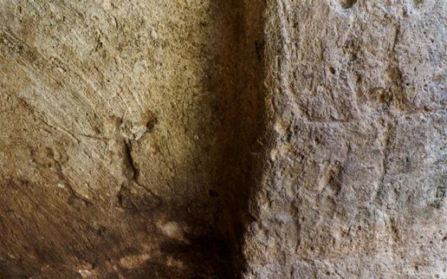Les gravures sur les murs du réservoir d'eau de Rosh HaAyin vieux de 2 700 ans, ici des personnages. (Crédit : Gilad Itach, IAA)