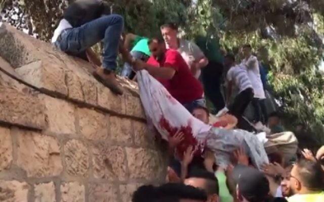 La dépouille enveloppée d'un drap ensanglanté de Muhammad Hassan Abu Ghanem peut être vue dans une vidéo postée sur les réseaux sociaux palestiniens (Crédit : capture d'écran Facebook)