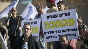 Des militants brandissent des pancartes pour protester contre le traitement des pères divorcés devant la Cour suprême de Jérusalem, le 6 décembre 2016 (Crédit : Yonatan Sindel/Flash90)