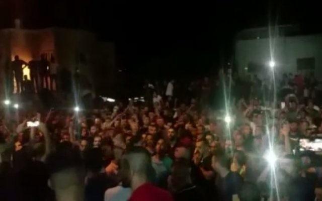 Quelque 3 000 personnes se sont rassemblées mercredi à Umm al-Fahm pour l'enterrement des trois Arabes-Israéliens qui ont abattu des agents de police druzes (Crédit : capture d'écran Dixième chaîne)