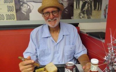 Alan Gross avec ce qu'il préfère, un sandwich au pastrami et un cigare cubain, à Loeb's Deli à Washington DC, le 12 juillet 2017. (Crédit : Ron Kampeas)