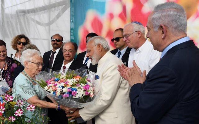 Le Premier ministre indien, au centre en blanc, reçoit un bouquet de fleurs pendant sa visite à la ferme Dan, accompagné du Premier ministre Benjamin Netanyahu, tout à droite, le 4 juillet 2017. (Crédit : Haim Tzach/GPO)