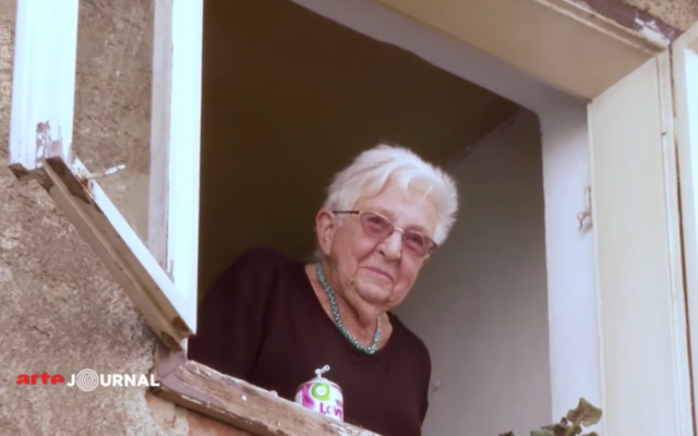 Nelly Guttmanova, aujourd'hui une kibboutsnik de 91 ans, à la fenêtre de sa maison d'enfance en Bohème, d'où elle fut déportée (Crédit: capture d'écran Arte)