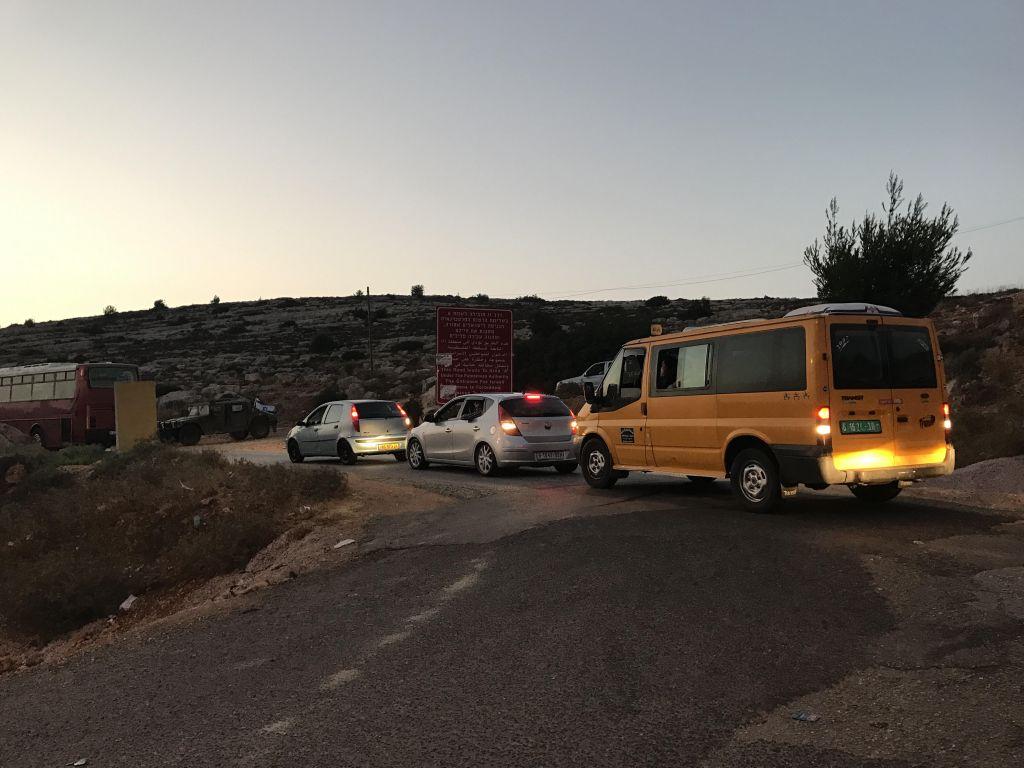 Les véhicules bloqués à l'entrée de Koubar, le village du terroriste palestinien qui a tué 3 Israéliens chez eux à Halamish, le 22 juillet 2017 (Crédit : Jacob Magid/Times of Israel)