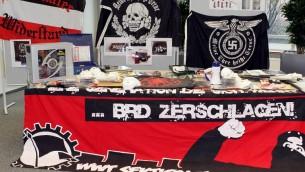 Des drapeaux, des masques, des armes et une bannière néonazis, sur laquelle il est inscrit 'Désintégrer la République fédérale d'Allemagne' pendant une conférence de presse à Hambourg, en Allemagne, le 2 mars 2012. (Crédit : Malte Christians/dpa/AFP)