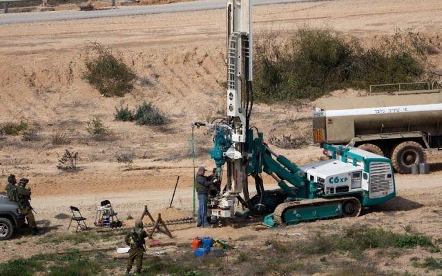 Cette photo datant du 10 février 2016 montre que les soldats de l'armée israélienne surveillent une machine qui forage pour creuser du côté israélien de la frontière avec la bande de Gaza alors qu'ils cherchent des tunnels utilisés par des terroristes palestiniens qui envisagent d'attaquer Israël (Crédit : AFP / Menahem Kahana)