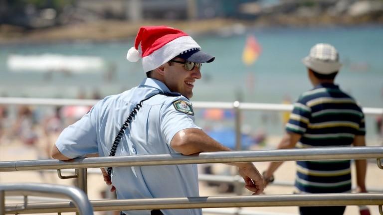 Un policier portant un chapeau de noël patrouille sur la plage de Bondi le jour de Noël à Sydney, en Australie, le 25 décembre 2016 (Crédit : AFP PHOTO / PETER PARKS)