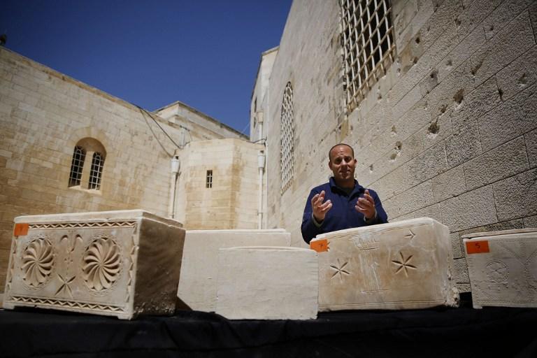 L'archéologue israélien Eitan Klein de l'unité de prévention des vols des antiquités à côté de 11 cercueils anciens contenant des os juifs de la période du Second temple après qu'ils ont été soustrait à des voleurs , le 31 mars 2014, au musée Rockefeller de Jérusalem (Crédit : GALI TIBBON/AFP)