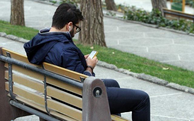 Un Iranien avec son smartphone dans un parc de Téhéran, le 1er décembre 2015. (Crédit : Atta Kenare/AFP)