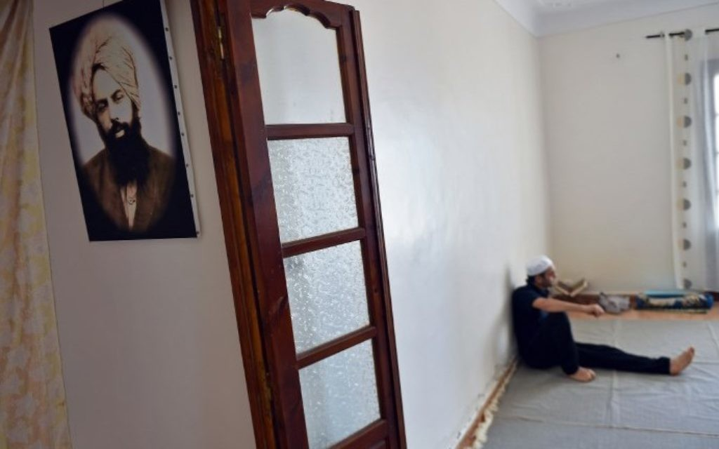 Un membre de la petite communauté ahmadie d'Algérie avec une photographie de Mirza Ghulam Ahmad, le fondateur du mouvement, dans une maison de Tilpasi, le 30 juin 2017. (Crédit : Ryad Kramdi/AFP)