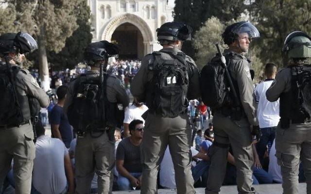 Les forces de sécurité israéliennes devant les palestiniens sur le mont du Temple à Jérusalem le 27 juillet 2017, avec la mosquée Al-Aqsa qui apparaît en arrière-plan (Crédit : AFP PHOTO / AHMAD GHARABLI)