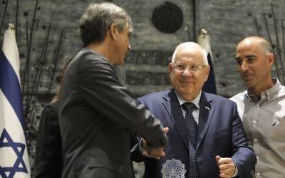 Le président Reuven Rivlin, au centre, pendant la remise d'un prix contre le racisme à Eli Ohana, à gauche, le président du Beitar Jerusalem, à la résidence présidentielle de Jérusalem, le 7 août 2017. (Crédit : Menahem Kahana/AFP)
