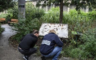 La police scientifique travaillant près de la plaque posée en mémoire des enfants et des adultes raflées à Izieu en avril 1944. La plaque a été vandalisée dans le nuit du 7 août 2017 (Crédit: AFP PHOTO / PHILIPPE DESMAZES)