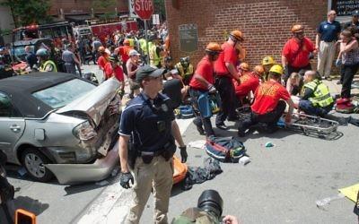 Secouristes et policiers sur les lieux d'une attaque à la voiture bélier, visible à gauche, conduite par James Fields, contre des manifestants anti-racisme, à Charlottesville, en Virginie, le 12 aout 2017. (Crédit : Paul J. Richards/AFP)
