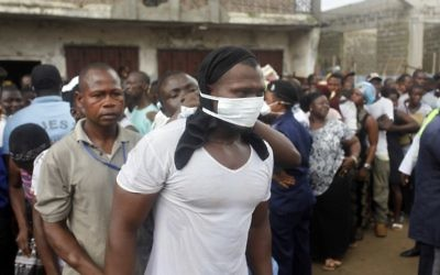 Des victimes des inondations cherchent à identifier leurs proches à la morgue de Freetown, la capitale de la Sierra Leone, le 16 août 2017. (Crédit : Saidu Bah/AFP)