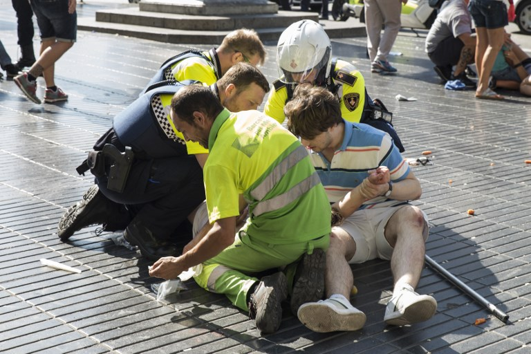 Des policiers et deux hommes viennent en aide à une victime après un attentat au cours duquel le conducteur d'une fourgonnette a dirigé son véhicule dans la foule, tuant au moins 13 personnes et faisant environ 100 blessés à la Rambla, à Barcelone, le 17 août 2017 (Crédit : Nicolas CARVALHO OCHOA/AFP PHOTO)