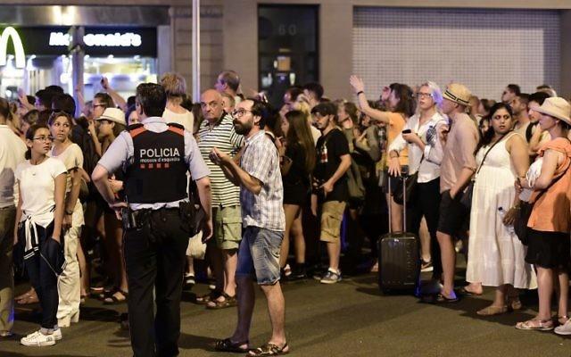 Les touristes attendent que la police les autorise à revenir dans leur hôtel sur le boulevard de  Las Ramblas après un attentat au véhicule-bélier qui a tué au moins 13 personnes et fait plus d'une centaine de blessés à Barcelone, le 18 août 2017 (Crédit : JAVIER SORIANO/AFP)