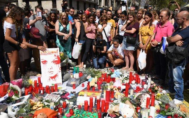 Des gens se recueillent auprès des fleurs, des bougies et autres objets posés sur le boulevard Las Ramblas à Barcelone alors qu'ils rendent hommage aux victimes de l'attentat de Barcelone le 18 août 2017. (Crédit : PASCAL GUYOT/AFP)