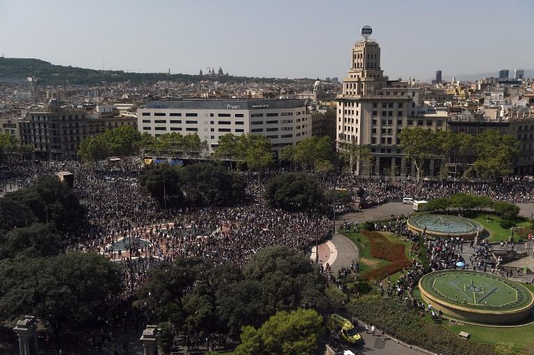 L'assistance quitte la Plaza de Catalunya après avoir observé une minute de silence pour les victimes de l'attentat de Barcelone le 18 août 2017, vingt-quatre heures après qu'une fourgonnette a foncé dans la foule, faisant 13 morts et blessant plus de 100 personnes dans le quartier Las Ramblas de Barcelone (Crédit :  / AFP PHOTO / LLUIS GENE)