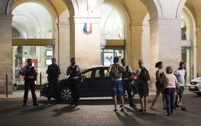 Passagers et policiers devant la gare de Nîmes après sa réouverture, le 19 août 2017. (Crédit : Jaime Reina/AFP)