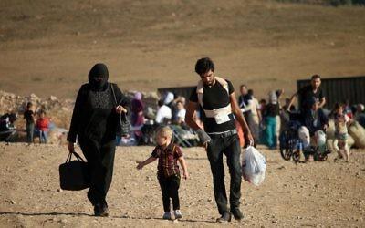 Réfugiés de retour en Syrie après l'entrée en vigueur d'un cessez-le-feu, près de Nasib, à la frontière syro-jordanienne, le 22 août 2017. (Crédit : Mohamad Abazeed/AFP)