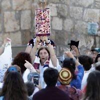 """Les membres de l'association """"Les femmes du mur"""" brandissent un rouleau de Torah durant un service de prière marquant le premier jour du mois juif d'Elul, au mur Occidental dans la Vieille Ville de Jérusalem, le 23 août 2017 (Crédit :Menahem Kahana/AFP Photo)"""