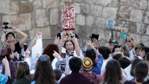 """Les membres de l'association """"Les femmes du mur"""" brandissent un rouleau de Torah durant un service de prière marquant le premier jour du mois juif d'Elul, au mur Occidental dans la Vieille Ville de Jérusalem, le 23 août 2017 (Crédit : Menahem Kahana/AFP)"""