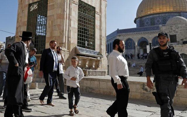 Le député Yehuda Glick (au centre, à gauche), marche pieds-nus, escorté par la police israélienne et des sympathisants, sur l'esplanade du mont du Temple, dans la Vieille Ville de Jérusalem Est, le 19 août 2017. (Crédit : Ahmad Gharabli/AFP)