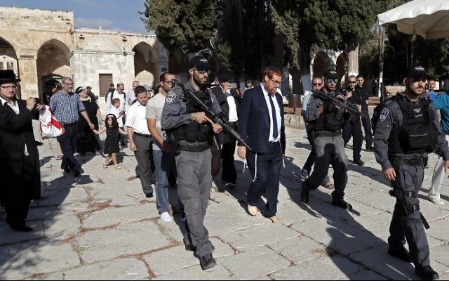 Le législateur Yehuda Glick, au centre, marche pieds nus, escorté par la police israélienne et des partisans, à l'intérieur du complexe sensible de la mosquée Al-Aqsa, connue également sous le nom du complexe du mont du Temple, dans la Vieille Ville de Jérusalem, le 29 août 2017 (Crédit : AHMAD GHARABLI / AFP)