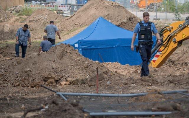 Un policier devant la tente bleue recouvrant une bombe britannique de la Seconde Guerre mondiale, retrouvée pendant des travaux à Francfort, le 30 août 2017. (Crédit : Boris Roessler/Germany OUT/dpa/AFP)