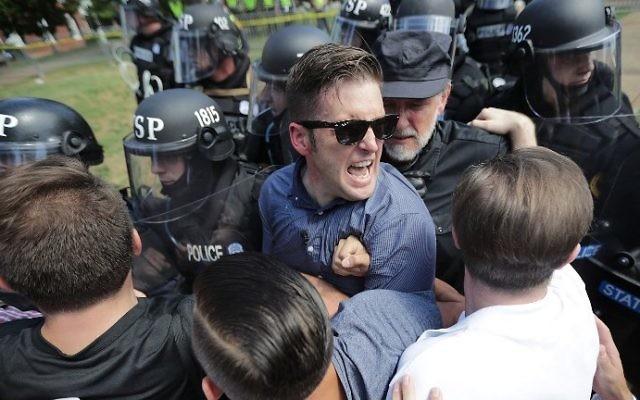 Le nationaliste blanc Richard Spencer, au centre, et ses partisans lors d'un affrontement contre la police de Virginie pendant un rassemblement d'extrême-droite à Charlottesville, le 12 août 2017. (Crédit : Chip Somodevilla/Getty Images/AFP)