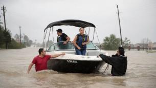 Des gens secourus d'un quartier inondé après les pluies torrentielles entraînées par l'ouragan Harvey, à Houston, au Texas, le 28 août 2017. (Crédit : Scott Olson/Getty Images/AFP)
