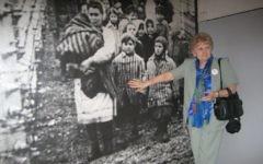 Eva Mozes Kor, jumelle de Mengele, devant sa photographie au musée du mémorial d'Auschwitz, en  2007. (Crédit : autorisation)