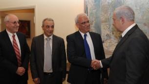 Le Premier ministre Benjamin Netanyahu serre la main de Saeb Erekat à Jérusalem en avril 2012. L'aide de Netanyahu  Yitzhak Molcho est à sa gauche, et le chef de la sécurité de l'AP est Majed Faraj second à gauche sur la photo. (Crédit : Amos Ben Gershom/GPO/Flash90)