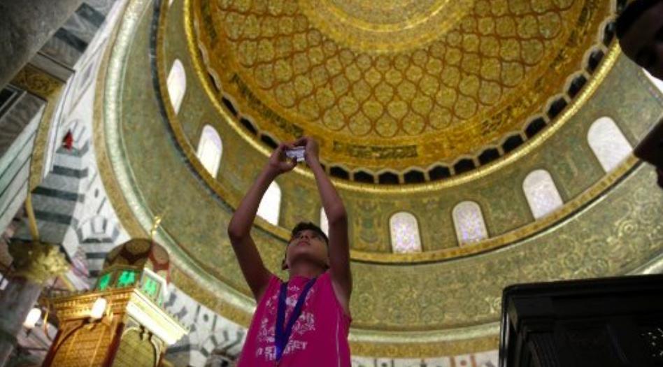 Un garçon palestinien de la bande de Gaza prend une photo dans le complexe de la mosquée Al-Aqsa dans la Vieille Ville de Jérusalem le 20 août 2017 alors qu'il visite la ville pour la première fois dans le cadre d'un programme d'échange dirigé par l'agence des Nations Unies pour les réfugiés palestiniens. (Crédit : AFP / AHMAD GHARABLI)