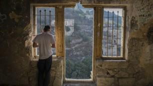 Un Juif orthodoxe récite la prière de Tashlich dans un bâtiment de Lifta, à l'entrée de Jérusalem, près de ka rivière de Lifta (Crédit : Yonatan Sindel / Flash90)