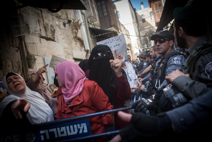 Des musulmanes palestiniennes du groupe des Mourabitounes crient et brandissent le Coran durant une manifestation contre les policiers israéliens qui les empêchent d'entrer sur le mont du Temple dans la Vieille Ville de Jérusalem le 17 septembre 2015 (Crédit : Miriam Alster/Flash90 )