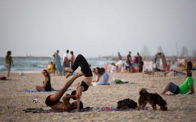 Des Israéliens profitent de la plage à Tel Aviv lors d'une vague de chaleur en Israël, le 16 mai 2016. Illustration. (Crédit : Miriam Alster/Flash90)