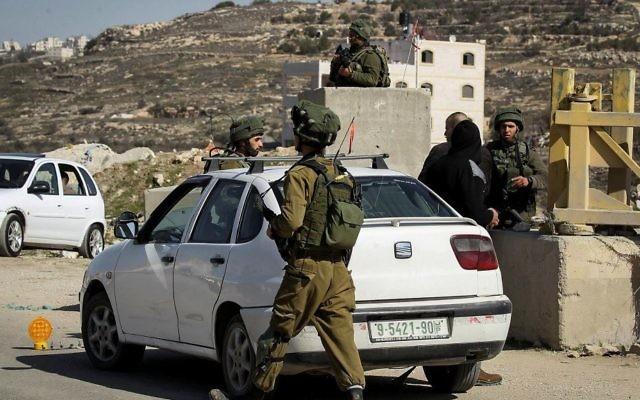 Illustration. Des soldats de l'armée israélienne contrôlent des voitures palestiniennes à un barrage routier situé dans le village de Yatta, en Cisjordanie, le 10 février 2017 (Crédit :Wisam Hashlamoun/Flash90)