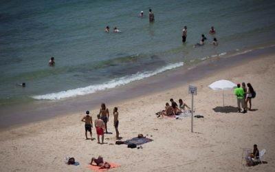 Des personnes profitant de la plage à Tel Aviv lors d'une chaude journée d'été, le 4 juillet 2017 (Crédit : Miriam Alster / Flash90)