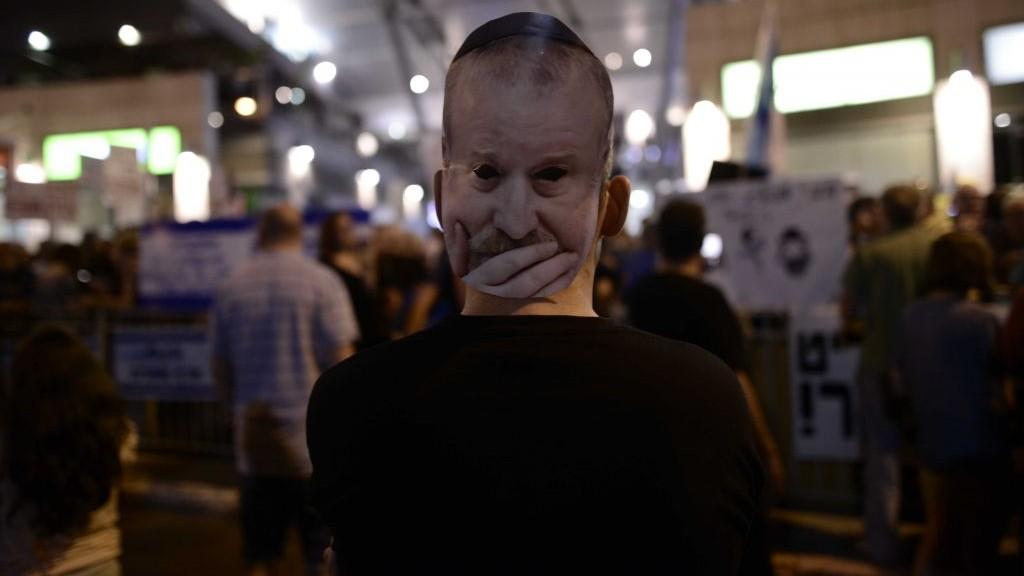 Un manifestant porte un masque du procureur général Avichai Mandelblit durant une manifestation contre le Premier ministre Benjamin Netanyahu aux abords de l'habitation de Mandelblit à Petah Tikva, le 22 juillet 2017 (Crédit : Tomer Neuberg/Flash90)