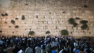 Des hommes juifs prient au mur Occidental, dans la Vieille Ville de Jérusalem, le 31 juillet 2017 pour marquer le début de Tisha B'av. (Crédit : Yonatan Sindel/Flash90)