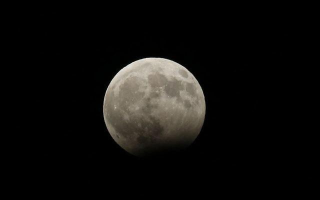 Pleine lune au début d'une éclipse partielle, vue depuis Hébron, en Cisjordanie, le 7 août 2017. (Crédit : Wisam Hashlamoun/Flash90)