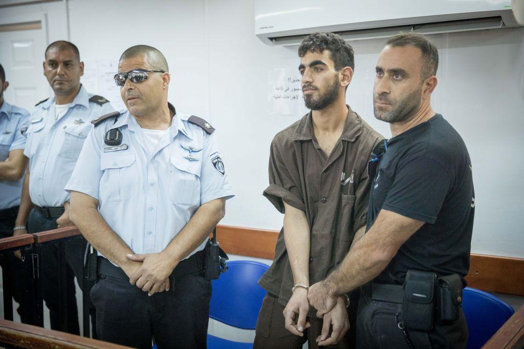 Omar Al-Abed, menotté, est présenté devant une salle d'audience pour son procès au tribunal militaire d'Ofer à proximité de Ramallah, en Cisjordanie, le 17 août 2017 (Crédit : Yonatan Sindel/Flash90)