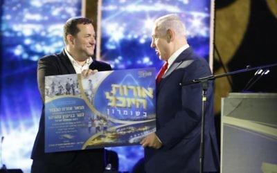 Le Premier ministre Benjamin Netanyahu, à droite, avec Yossi Dagan, leader du mouvement des implantations, lors d'un événement commémorant  50 années d'implantation en Cisjordanie, le 28 août 2017. (Crédit : Jacob Magid/Times of Israël)