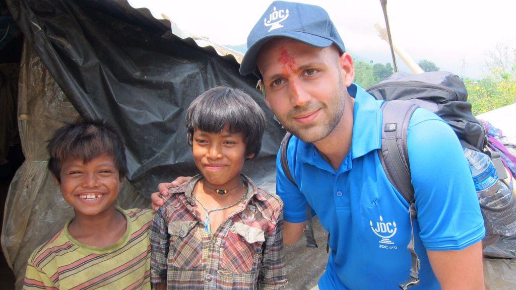 Eliran Douenias, un bénévole israélien du Joint Distribution Committee basé à Katmandou avec des enfants lors d'une de ses visites sur le terrain, après avoir participé à une cérémonie religieuse traditionnelle (Crédit : Eliran Douenias / JDC)